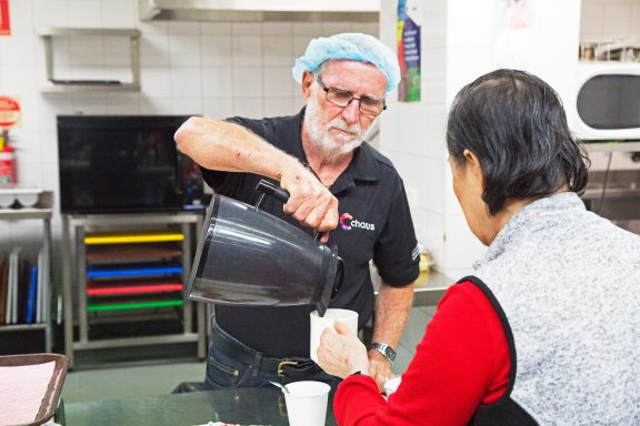 A volunteer at Chorus Kitchen pours a cup of tea for a customer
