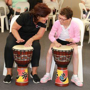 Chorus staff drumming with customer