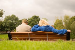 A woman sits beside an older man on a bench in a park, talking about what he's struggling with and how to get back on track.