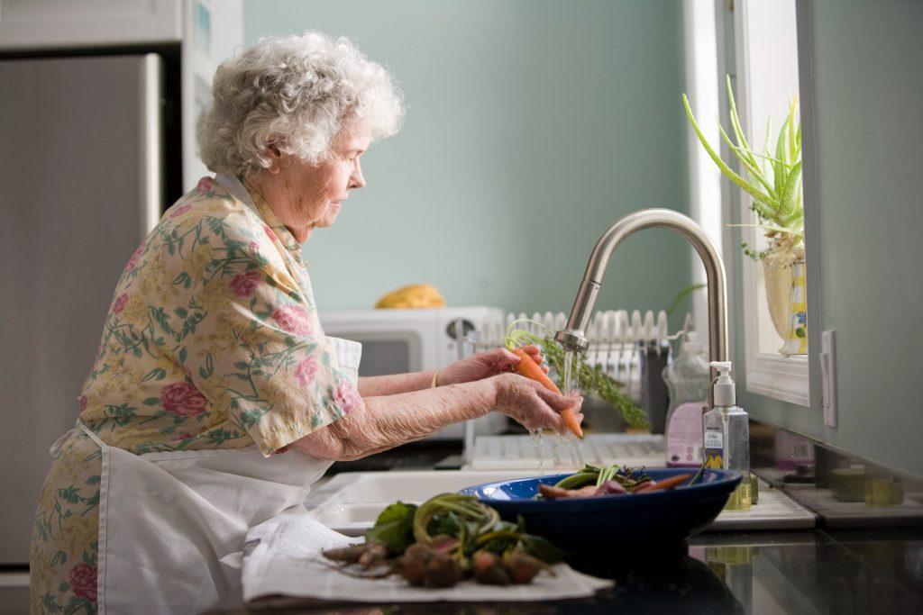 Image of older person washing vegetables