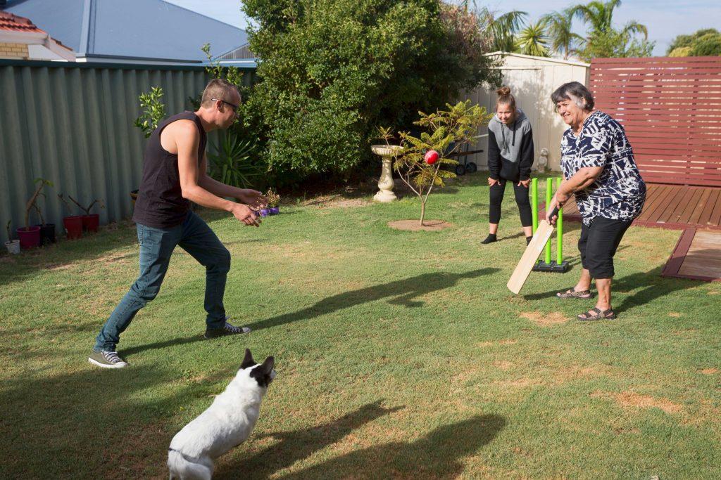 Family, including grandmother, playing backyard cricket