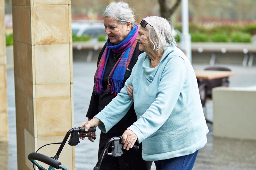 support worker walking with customer using a walker