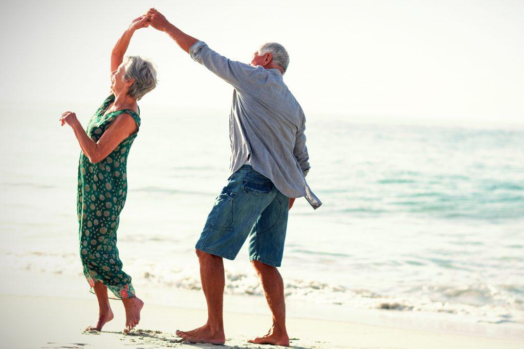 older couple exercising on beach
